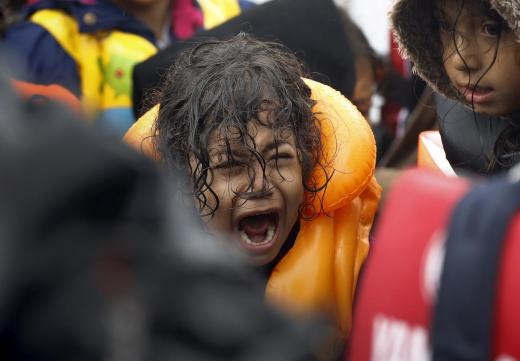 A Syrian refugee child screams inside an overcrowded dinghy after crossing part of the Aegean Sea from Turkey to the Greek island of Lesbos