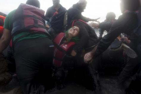 Syrian refugee struggles to get off an overcrowded dinghy as refugees and migrants arrive in rough sea on the Greek island of Lesbos, after crossing a part of the Aegean Sea from the Turkish coast