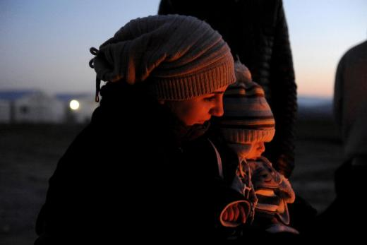 A Syrian refugee holds her baby next to a bonfire as she waits to cross the Greek-Macedonian border, near the village of Idomeni