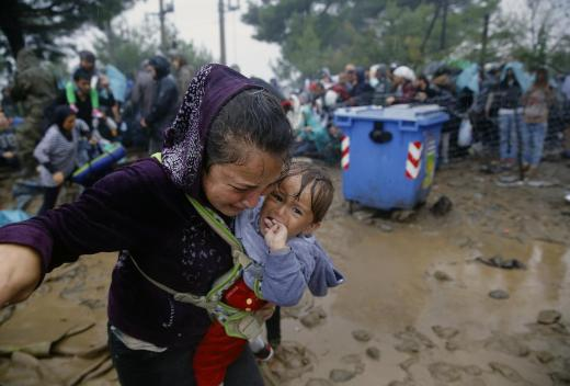 A Syrian refugee cries as she carries her baby walking through the mud to cross the border from Greece into Macedonia during a rainstorm